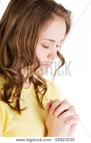 Young pretty caucasian girl praying over white background.