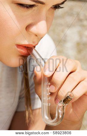 Teen Girl smoking cannabis outdoor.