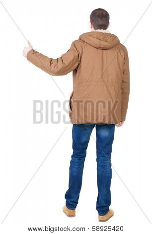 Back view of handsome man in winter jacket  shows thumbs up. Standing young guy in parka. Rear view people collection.  backside view of person.  Isolated over white background.