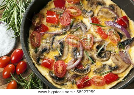 Vegetable omelet cooked in a skillet or frypan.  Mushrooms, capsicum, baby plum tomatoes and red onion. Top view.