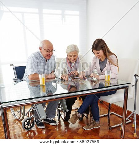 Family with happy senior couple playing jigsaw puzzle at home