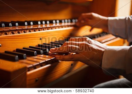 Detail of a man playing a church organ