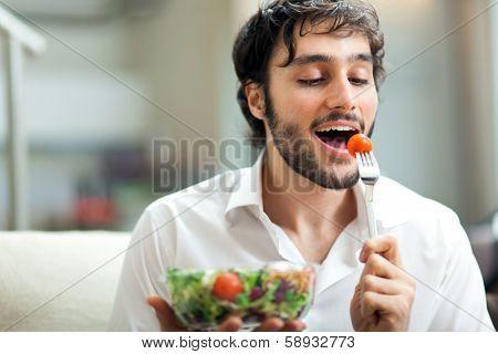 Young man eating a healthy salad