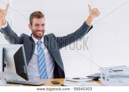 Portrait of a cheerful young businessman gesturing thumbs up by computer at office desk