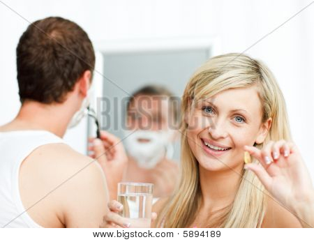 Smiling Woman Holding Pills And Man Shaving