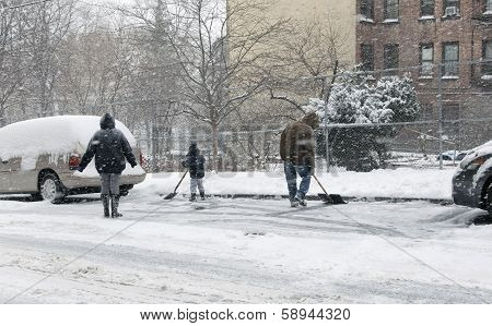 Family Shoveling During Snow Storm In New York
