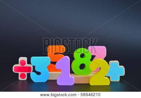 Color wooden blocks in the shapes of numbers. Dark shiny background with reflexions. Numbers with path.