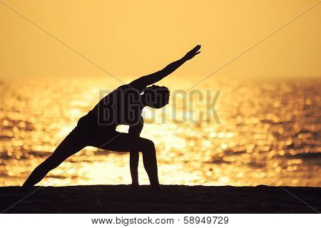 Man practicing yoga on ocean beach
