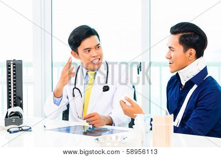 Asian doctor showing patient with toby collar his radiograph in medical practice or surgery