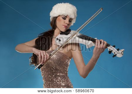 Beautiful woman in an elegant silver dress and white furry winter hat standing playing a violin against blue sky with a look of complete enjoyment and absorption