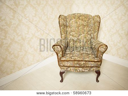 Stylish empty upholstered gold vintage armchair standing in the corner of a room with wallpapered walls in a matching gold