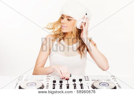 Beautiful young blond female DJ wearing headphones standing at her mixing desk and turntables