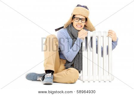 Freezing young guy in winter hat and scarf sitting next to radiator isolated on white background