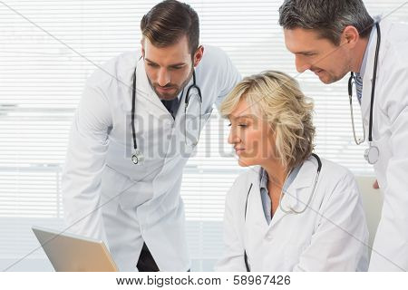 Three concentrated doctors using laptop together at the medical office