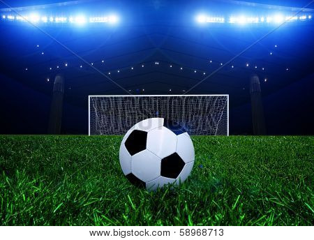 Soccer ball on the penalty point in a stadium at night