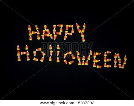 Happy Holloween made with candy corn on black back ground