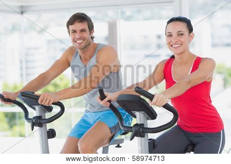 Smiling young couple working out at class in a bright gym