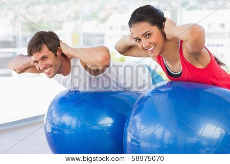 Fit young couple exercising on fitness balls in the bright gym
