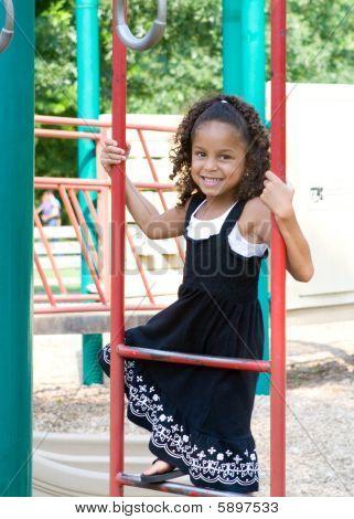 A Beautiful Mixed Race Child Enjoying The Playground