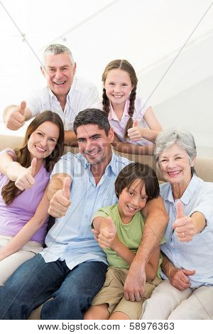 Portrait of happy multi-generation family gesturing thumbs up at home