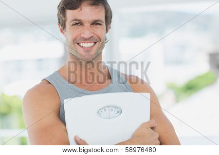 Portrait of a fit young man standing with scale in a bright exercise room