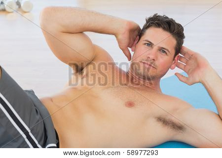 Determined young man doing abdominal crunches on exercise mat at a gym