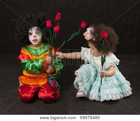 little girl gives flowers to the boy - clown, african