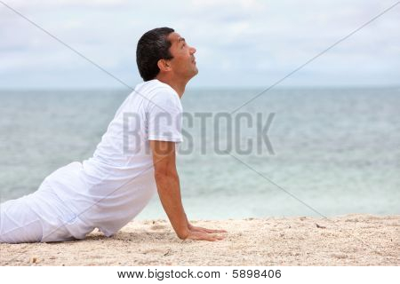 Fit Man Doing Yoga At The Beach