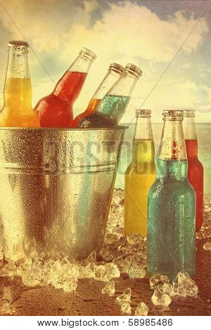 Cool summer drinks in ice bucket at the beach with vintage look