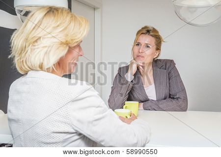 Two woman talking about the latest gossip on their coffeebreak in the office attentively listening to eachother