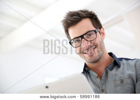 Man with eyeglasses websurfing with touchpad