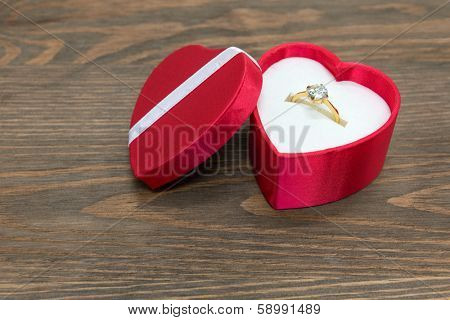 Diamond engagement ring in a red silk heart shaped box.
