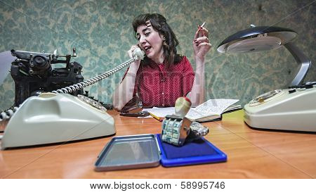 young Secretary smoking a cigarette while talking on the phone 1960's scene