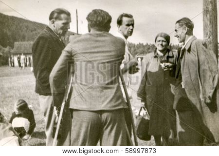 WEGIERSKA GORKA, POLAND, CIRCA FORTIES - Vintage photo of men (one of them with orthopedic sticks) and a boy