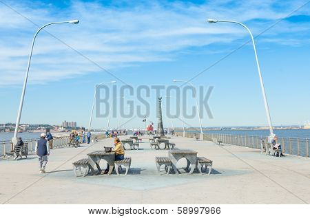 BROOKLYN, USA - OCTOBER 8, 2013: People resting and fishing at Pier 69 in Bay Ridge, Brooklyn, with the September 11 Beacon Memorial in background