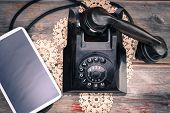 stock photo of rotary dial telephone  - Tablet computer with a blank screen lying alongside a retro rotary telephone with its handset off the hook on a decorative doily high angle view - JPG