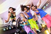 stock photo of zumba  - young women in sport dress jumping at an aerobic and zumba exercise - JPG