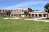 picture of school building  - exterior of modern red brick school by a lush green lawn - JPG