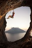stock photo of fail-safe  - Female rock climber falling of a cliff while lead climbing - JPG