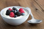 stock photo of yogurt  - Bowl of fresh mixed berries and yogurt with farm fresh strawberries blackberries and blueberries served on a wooden table - JPG