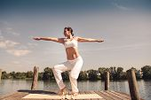 picture of tai-chi  - young woman making tai chi exercise at a lake - JPG