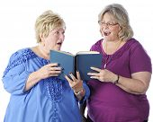 Two senior women singing from the same book.  One looks at the music happily while the other scowls
