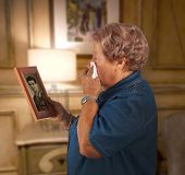image of deceased  - Old lady crying watching a photo of a deceased person - JPG