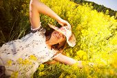 picture of wildflower  - Happy woman lying among yellow wildflowers in summer - JPG