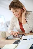 pic of 35 to 40 year olds  - Woman working from home on digital tablet - JPG
