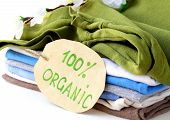 image of naturalist  - stack of multicolored clothing with 100% organic label