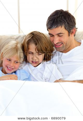 Attentive Father And His Children Reading Book