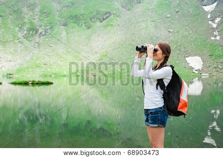 Young woman admiring the beautiful view of the lake and mountains through a binocular.