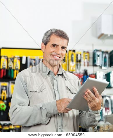 Portrait of confident mature man using tablet computer in hardware store