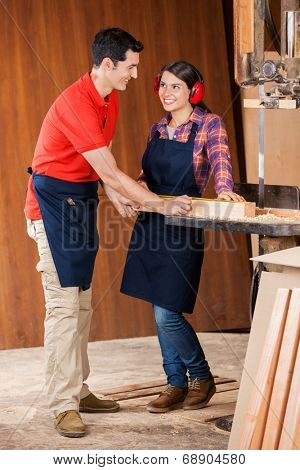 Happy male and female carpenter measuring wooden plank while looking at each other in workshop